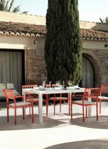 Mesa clara con sillas naranja, catalogo out Gabar